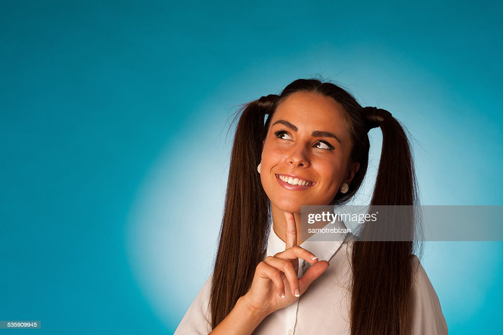 Pensativo joven mujer pensando en frente de fondo azul : Foto de stock
