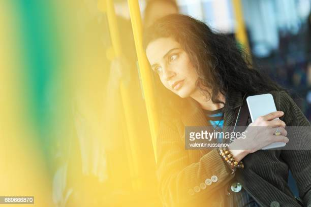 Pensive young woman traveling and holding smart phone