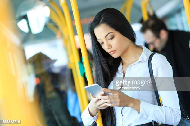 Pensive young woman using smart phone in a bus