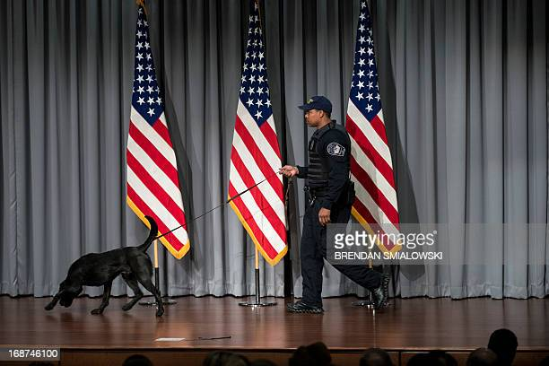 A Pentagon Police Officer checks a stage with a dog before US Secretary of Defense Chuck Hagel speaks about furloughs during a town hall style...