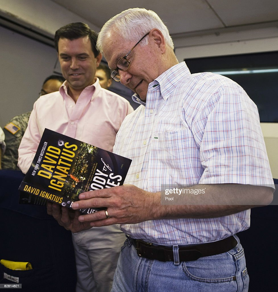 Pentagon Press Secretary Geoff Morrell (L) looks on as US Secretary of Defense Robert Gates (R) looks over a copy of 'Body of Lies' presented as a gift by Washington Post reporter and author David Ignatious (not pictured), part of the press corps traveling with the secretary, aboard a USAF 747-E4B airborne command post September 14, 2008 while over the Atlantic Ocean enroute to Incirlik Air Force Base in Turkey.