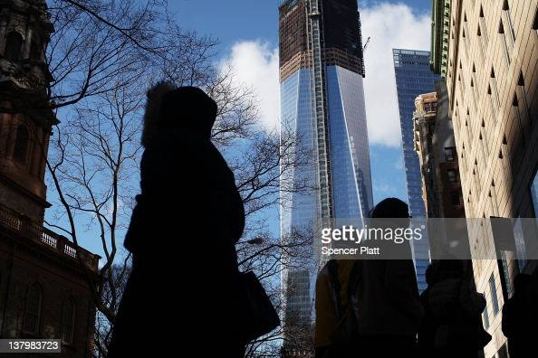 Peole walk past One World Trade Center the central skyscraper under construction at Ground Zero on January 30 2012 in New York City The price tag for...