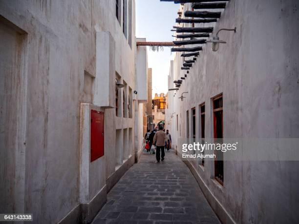 peole walking in an alleyway in Souq Waqif, Doha, Qatar - February 3, 2017