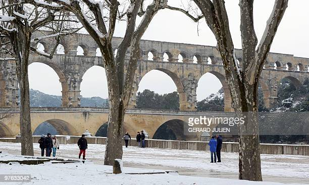 Peolpe walk near the Pont du Gard in Remoulins southern France on March 08 after heavy snow falls on the south of France AFP PHOTO/GERARD JULIEN