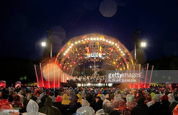 Peope attend the Vienna Philharmonic summer night open air concert conducted by US conductor Lorin Maazel on a rainy evening at the Schonbrunn Palace...