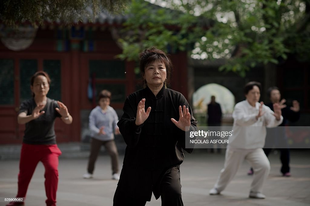 Peopl practice Tai Chi next to the Houhai lake in Beijing on April 29, 2016. / AFP / NICOLAS
