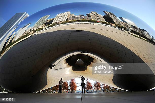 People admire 'Cloud Gate' by British artist Anish Kapoor at the ATT Plaza in Millennium Park that reflects the downtown skyline in Chicago Illinois...