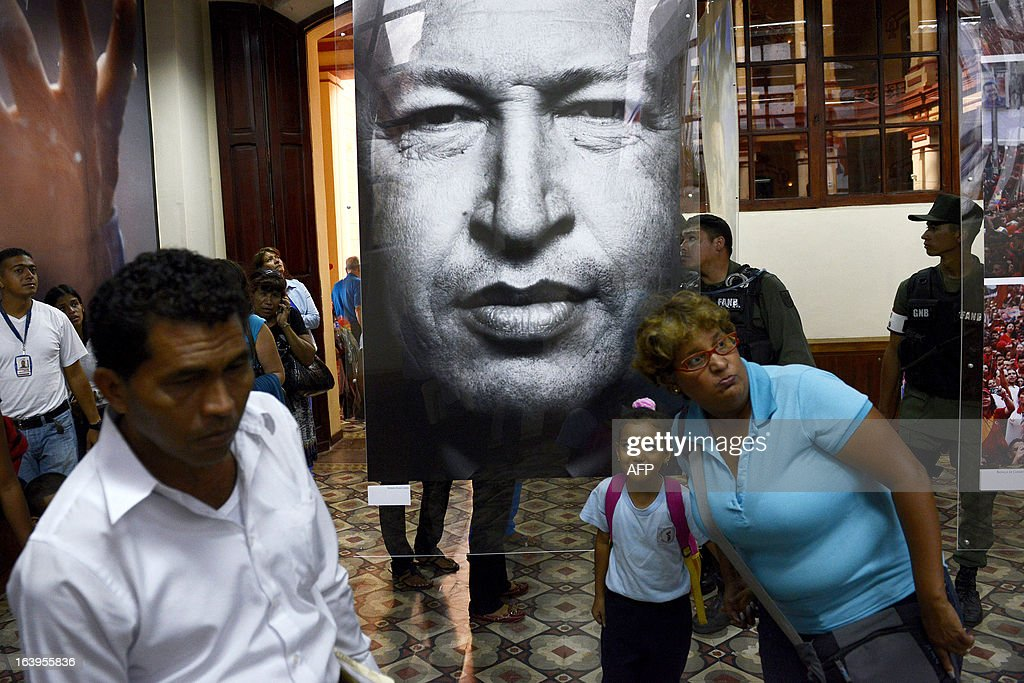 People admire photos of the late Venezuelan President Hugo Chavez at an exhibit near his remains at the 'Quarter of the Mountain' in the 23 de Enero Chavez bastion, in Caracas, on March 18, 2013. The 'Quarter of the Mountain', where the body of Chavez lies, while deciding on its transfer to the National Pantheon, is a former barracks that was the center of operations of the failed coup led by Chavez on February 4, 1992.