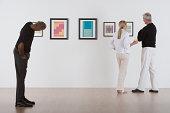 People admiring artwork in gallery