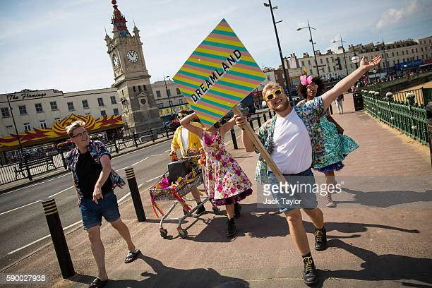 People advertising Dreamland amusement park play music and carry a placard along the promenade on August 16 2016 in Margate England British...
