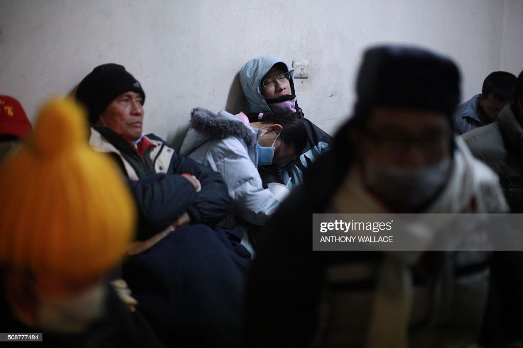 People affected by the collapse of a building rest in a room near the site of the disaster in the southern Taiwanese city of Tainan early on February 7, 2016 following a strong 6.4-magnitude earthquake. More than 250 people have been rescued from the Wei-kuan apartment complex in the southern city of Tainan since the quake hit at 4:00 am Saturday, killing 14 people and toppling four blocks of around 100 homes in total. WALLACE