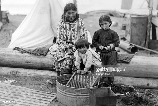 circa 1920 Eskimo children helping their mother on washing day