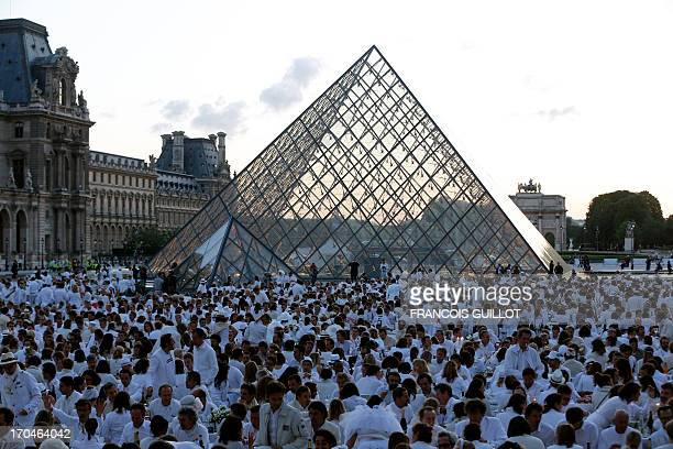 People all dressed up in white have a dinner on June 13 on the Louvre museum's square in Paris The venue of the 25th edition of the annual 'dinner in...