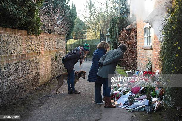 People and a dog look at the flowers and tributes outside the Oxfordshire home of British pop singer George Michael on December 27 2016 in Goring...