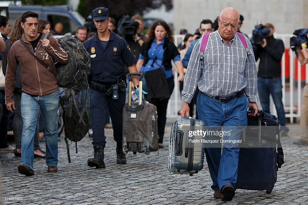 People and a policeman carry passengers' belongings collected from Rosalia de Castro Sport Center on July 27, 2013 in Santiago de Compostela, Spain. The crash occurred as the train approached the north-western Spanish city of Santiago de Compostela at 8.40pm on July 24th, at least 78 people have died and a further 131 reported injured. The crash occurred on the eve of the Santiago de Compostela Festivities.The driver has been formally accused of reckless homicide and remains in custody awaiting an appearance in court.