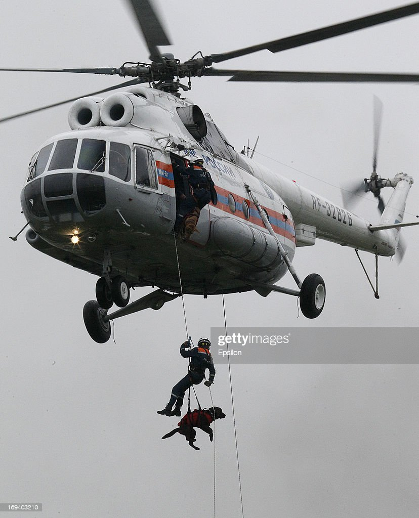 People and a resuce dog are lowered from a helicopter as the Russian Emergency Situations Ministry carry out simulation exercises at their Rescue Training Centre on May 24, 2013 in Noginsk, outside Moscow, Russia.