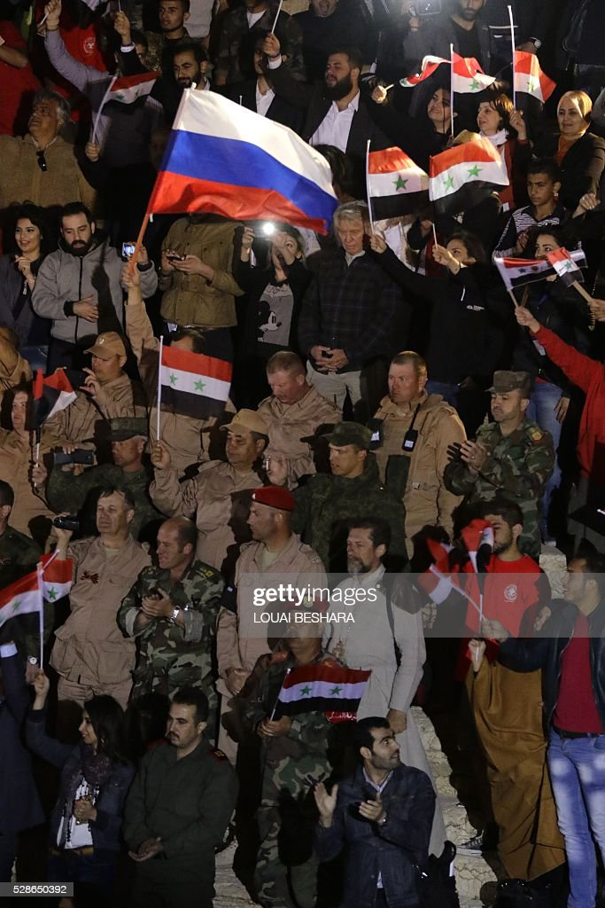 People and army personnel wave Syrian national flags as they attend a music concert in the ancient theatre of Syria's ravaged Palmyra on May 6, 2016 following its recapture by regime forces from the Islamic State group fighter. Syrian troops backed by Russian air strikes and special forces on the ground recaptured UNESCO world heritage site Palmyra from Islamic State (IS) group fighters in March 2016. BESHARA