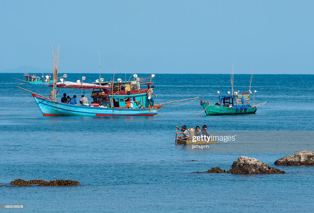 People and boats moving at the fishery harbor : Stock Photo