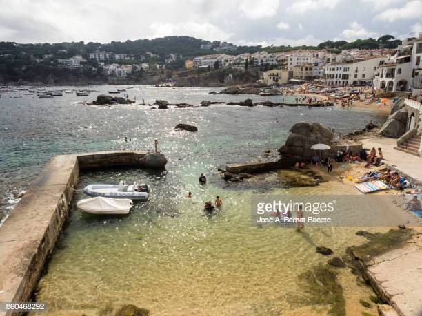 People and Caleya beach close to the sea with tourists in summer, bathing and sunbathing next to the fishing boats.  Calella, Coast Brava, Girona, Spain