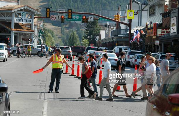 People and cars make their way through the main Square on August 20 2017 in Jackson Wyoming People are flocking to the Jackson and Teton National...