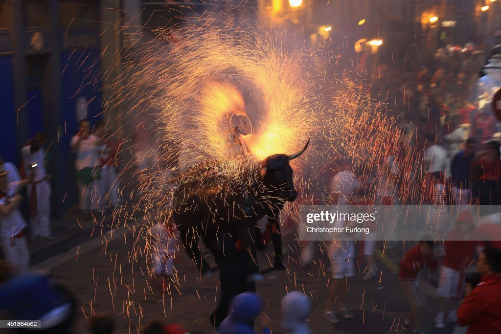 People and children are chased by a Toro del Fuego (flaming bull) as it is runs through the streets of Pamplona on the third day of the San Fermin Running Of The Bulls Festival on July 8, 2014 in Pamplona, Spain. The annual Fiesta de San Fermin, made famous by the 1926 novel of US writer Ernest Hemingway 'The Sun Also Rises', involves the running of the bulls through the historic heart of Pamplona.