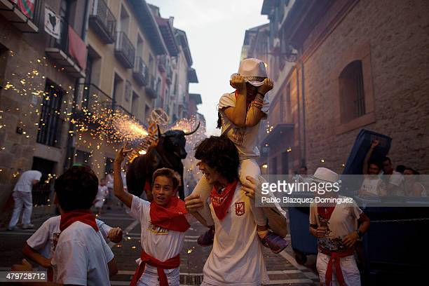 People and children are chased by the 'Toro de Fuego' as it runs throught the streets during the opening day of the San Fermin Running of the Bulls...