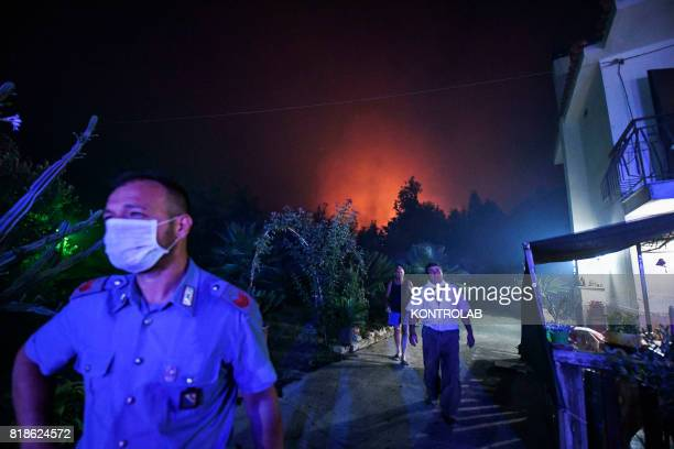 People and cops near a house threatened by flames during a vast fire that threatened the areas inhabited between Naples and Campi Flegrei throughout...