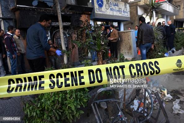 TOPSHOT People and investigators gather at the scene of a petrol bomb attack on a Cairo disco in the Agouza neighbourhood of the Egyptian capital's...