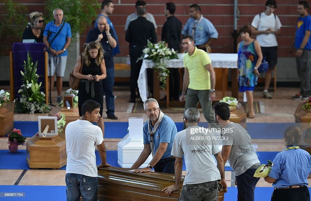 People and Italian scouts help to carry coffins of earthquake victims in a gymnasium arranged in a chapel of rest on August 26 in Ascoli Piceno two...