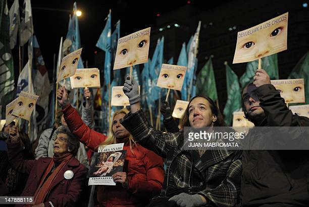 People and members of human rights organizations watch on a giant screen outside the court the reading of the sentences against two former Argentine...