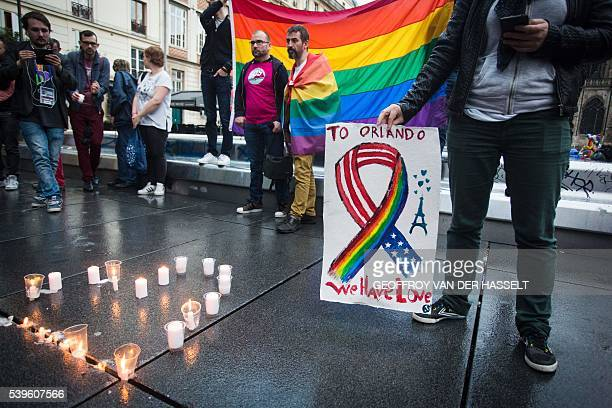 People and members of the gay community gather for a vigil near the Beaubourg art center in downtown Paris on June 12 to mourn for victims of the...