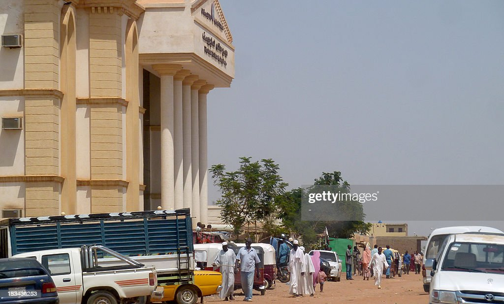 People and parked vehicles are see outside the courthouse in Haj Yousef district in the Sudanese capital Khartoum on October 6 2013 A judge threw out...