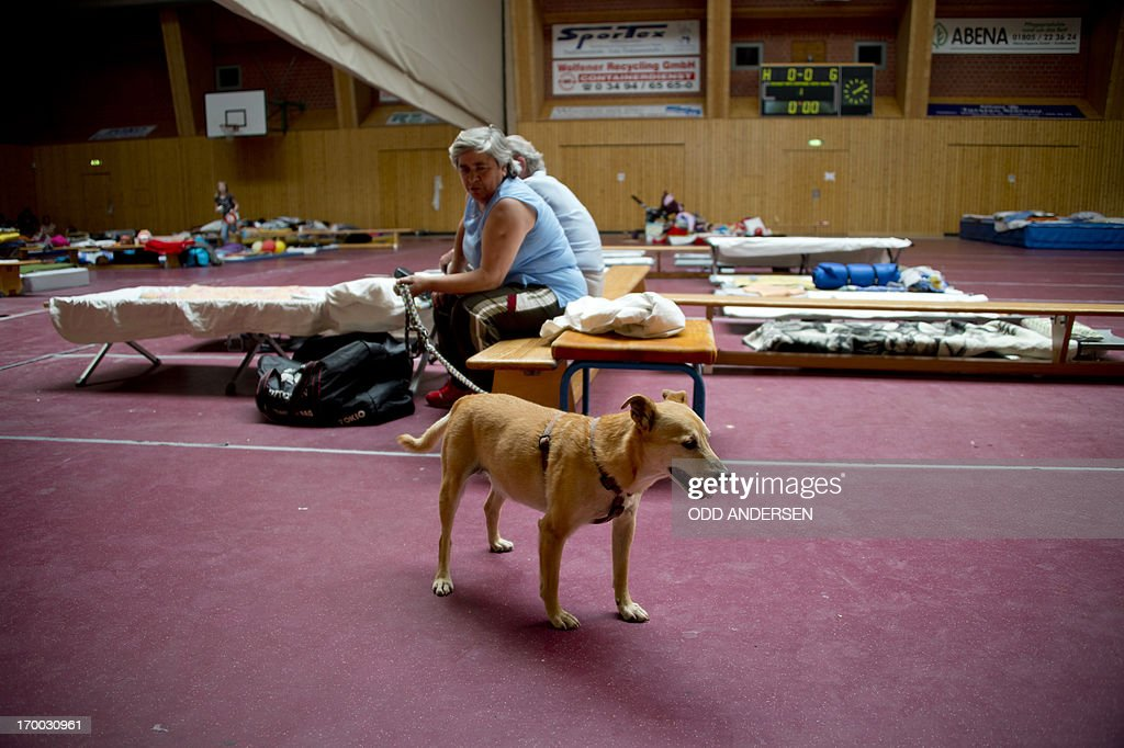 People and pets fleeing their homes as the flood waters rose take refuge in a sports hall used as makeshift accomodation in Bitterfeld, eastern Germany, on June 6, 2013. Germany pushed on with frantic efforts to secure saturated river dykes with sandbags bracing for a surge of the worst floods in over a decade that have claimed 12 lives and forced mass evacuations across central Europe. AFP PHOTO / ODD ANDERSEN