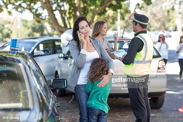 People and policeman at car accident scene