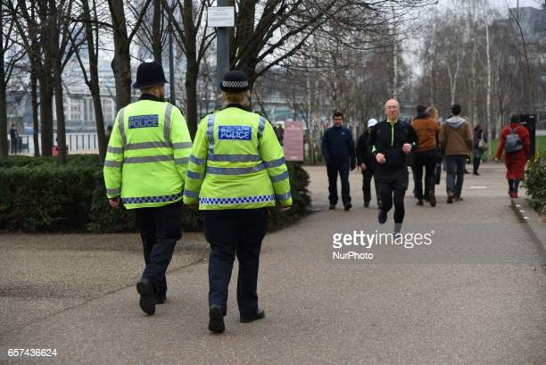 People and policemen are seen on a street leading to the Houses of Parliament in central London on March 24 2017 two days after the March 22 terror...