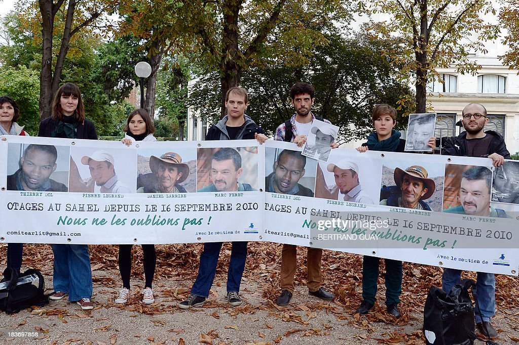 People and relatives of the family of the French hostage in Mali, Pierre Legrand, hold a banner showing portraits of the four French hostages kidnapped by Al-Qaeda in the Islamic Maghreb (AQMI) in 2010 in Niger and held in Mali, during a gathering for the hostages' support on October 9, 2013 near the Elysee presidential Palace in Paris.