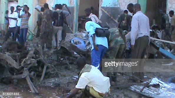 People and soldiers search in the rubble of a destroyed building on 28 February 2016 in Baidoa after twin explosions in the Somali city killed at...