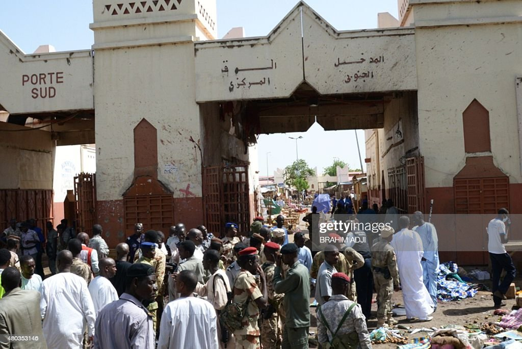People and soldiers stand outside a market in N'Djamena following a suicide bomb attack on July 11 2015 At least 14 people were killed in a suicide...