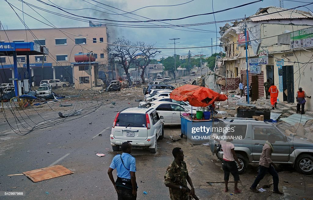 People and Somali security forces walk across the scene of a car bomb attack claimed by Al-Qaeda-affiliated Shabaab militants which killed at least 5 people, on the Naasa Hablood hotel in Mogadishu on June 25, 2016. The hotel in southern Mogadishu is often used by politicians and members of the Somali diaspora visiting the city. The attack came just three weeks after another assault quickly claimed by the Al-Qaeda-linked Shabaab group on the city's Ambassador hotel left 10 dead including two lawmakers when a huge car bomb ripped the front off the six-storey building. / AFP / MOHAMED
