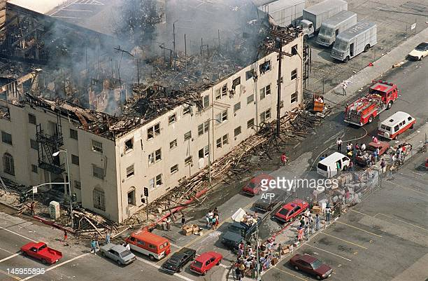 People and their belongings line a sidewalk across from a burned out apartment 01 May 1992 in Los Angeles The apartment was attached to a row of...