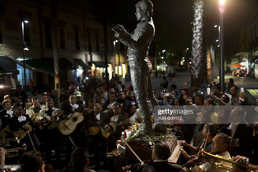 People and traditional Mexican mariachis perform around the statue of Mexican singer and composer 'Juan Gabriel' at the Plaza Garibaldi on August 28...