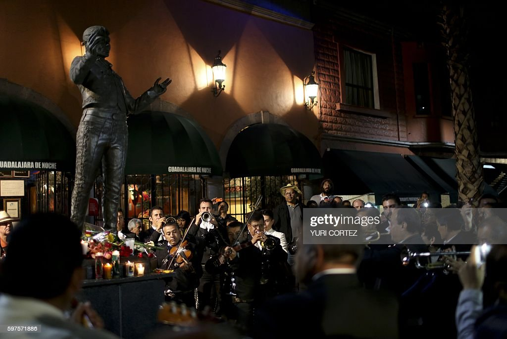 People and traditional Mexican mariachis perform at the statue of Mexican singer and composer 'Juan Gabriel' at the Plaza Garibaldi on August 28 2016...