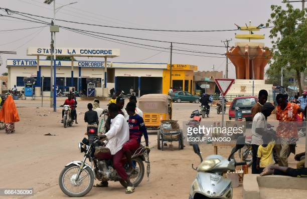 People and traffic move along a street in Agadez northern Niger on April 5 2017 Agadez the gateway to the desert a crossroads where thousands of...
