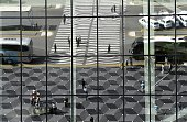 People and vehicles are reflected in the glass on the front of the Heydar Aliyev airport in Baku on June 9 ahead of the opening of the Baku 2015...