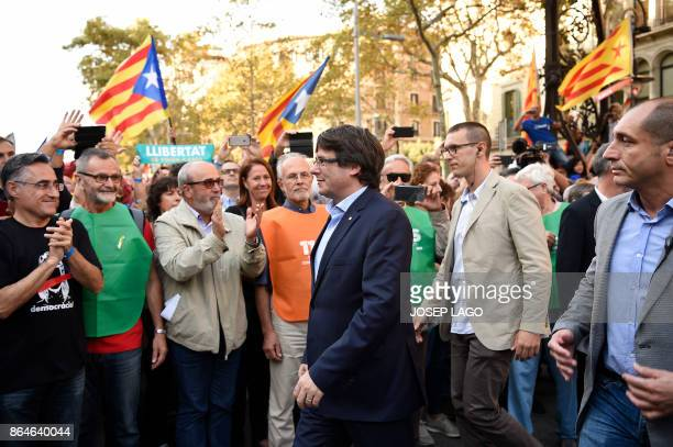 People applaud as Catalan regional president Carles Puigdemont arrives to attend a demonstration on October 21 2017 in Barcelona to support two...