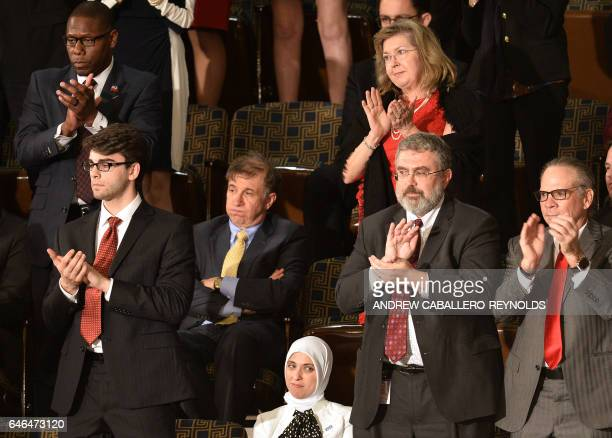 People applaud as US President Donald Trump addresses a joint session of the US Congress as others stay seated in disagreement on February 28 in...