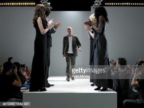 People applauding fashion designer on catwalk : Stock Photo