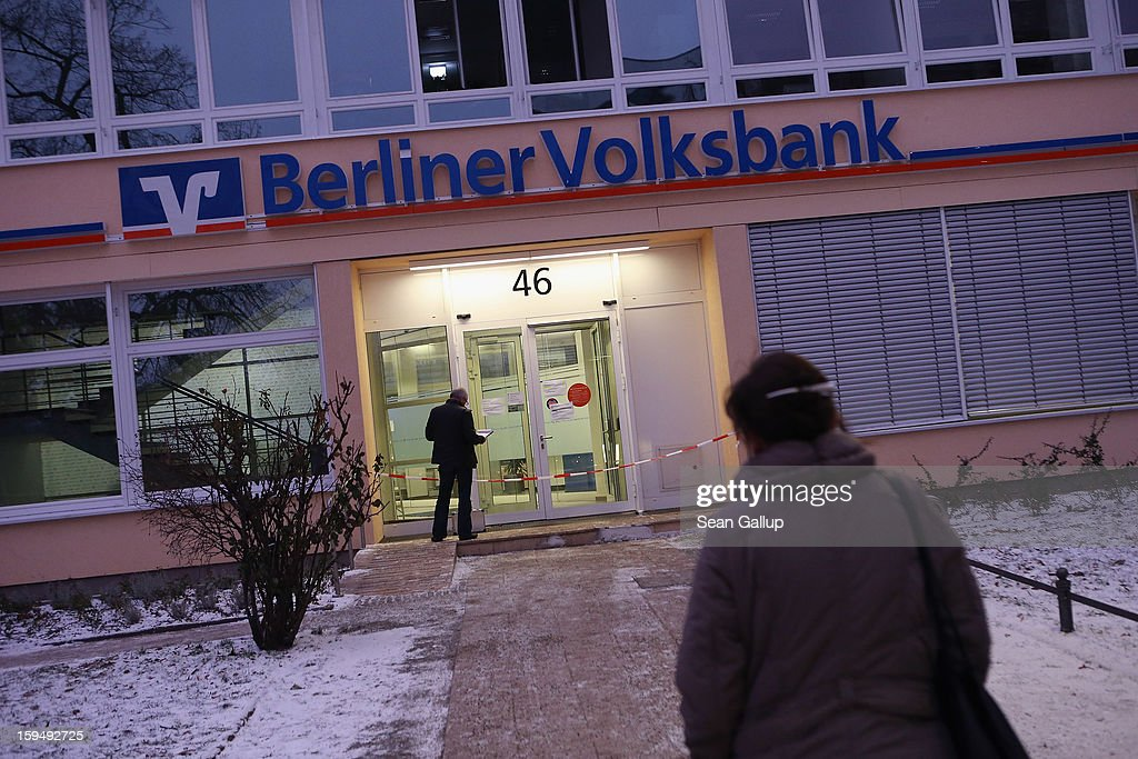 People approach a locked Steglitz district branch of Berliner Volksbank following a robbery of the bank that likely occured in the early morning hours on January 14, 2013 in Berlin, Germany. According to police the robbers dug a 30 meter long tunnel from a nearby underground parking garage to access the vault of the bank and made off with the contents.