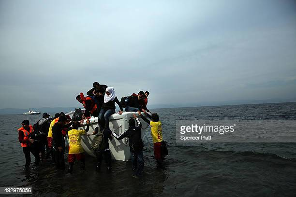People are assisted after arriving from Turkey on a raft onto the island of Lesbos on October 16 2015 in Sikaminias Greece Dozens of rafts and boats...