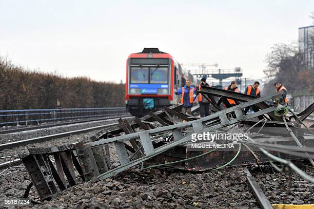 People are at work on December 21 2009 around the IledeFrance Paris regional train 'Transilien' which derailed after a car swerved on ice and hit a...